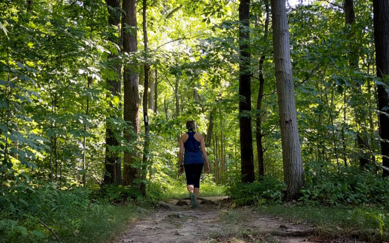 Lindsay Walking Between Trees in the Woodend Conservation Area :: I've Been Bit! Travel Blog
