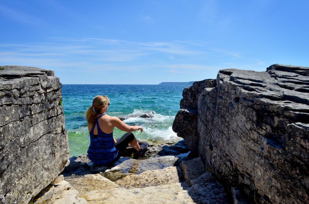 Lindsay sitting on the shores of Georgian Bay in Bruce Peninsula National Park :: I've Been Bit! Travel Blog