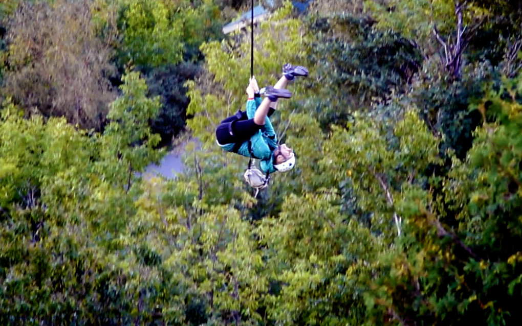 Lindsay rocking the zipline at Scenic Caves Nature Adventure as she hangs upside down from the line :: I've Been Bit! Travel Blog