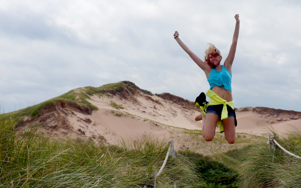 Lindsay jumping in front of the Greenwich Dunes on Prince Edward Island :: I've Been Bit! Travel Blog