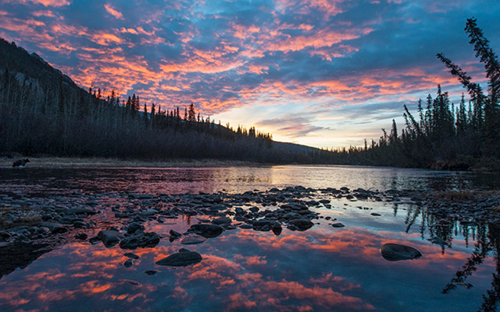 Sunset reflecting off a river in the Yukon, often a bucket list destination for many visiting Canada :: I've Been Bit! Travel Blog