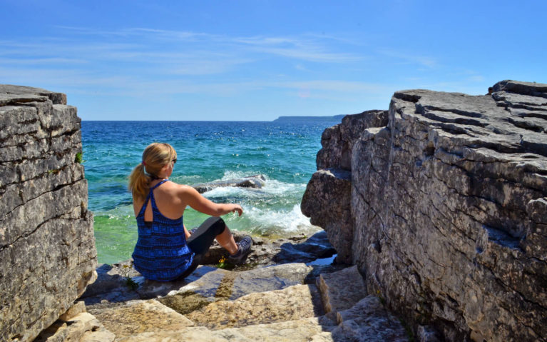 Lindsay sitting along the shores of Georgian Bay near Halfway Log Dump in Bruce Peninsula National Park :: I've Been Bit! Travel Blog