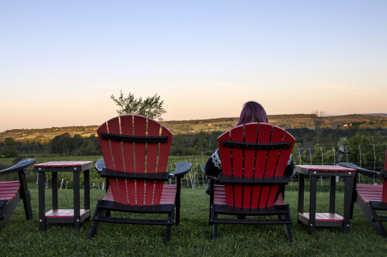 Lindsay enjoying the sunrise at Coffin Ridge Winery The Resting Place Overlooking Vineyards from Red Chairs :: I've Been Bit! A Travel Blog