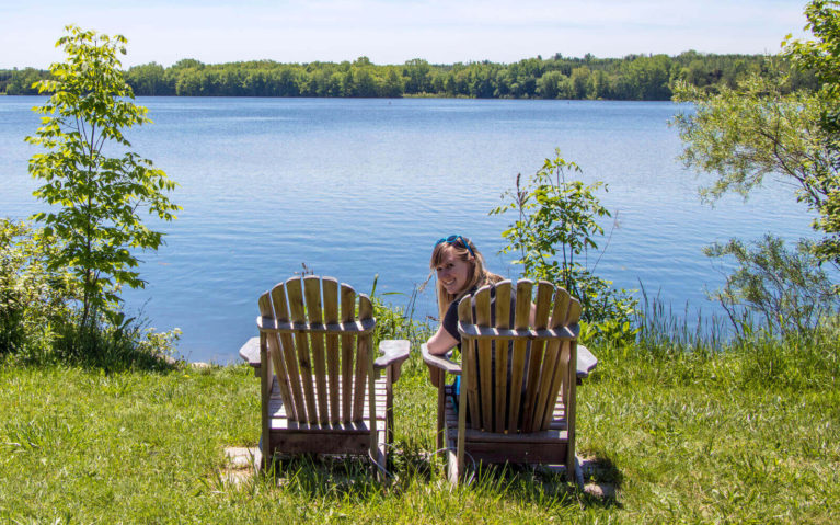Lindsay Sitting in Muskoka Chairs by the Lake at the Wildwood Conservation Area in Perth County :: I've Been Bit! Travel Blog