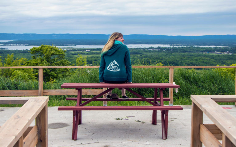 Lindsay Sitting on a Picnic Table at the Macleans Mountain Lookout, Manitoulin Island Ontario :: I've Been Bit! Travel Blog