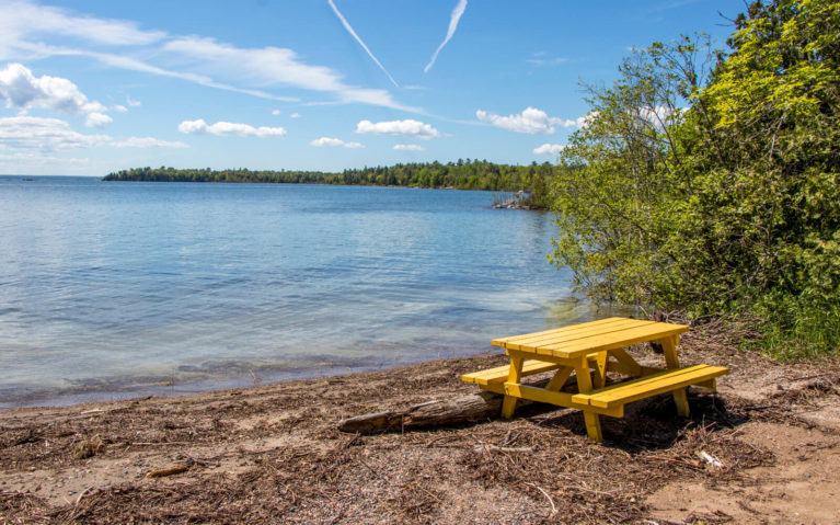 Beach with Yellow Picnic Bench In Front of the Turquoise Water of Lake Huron :: I've Been Bit! Travel Blog