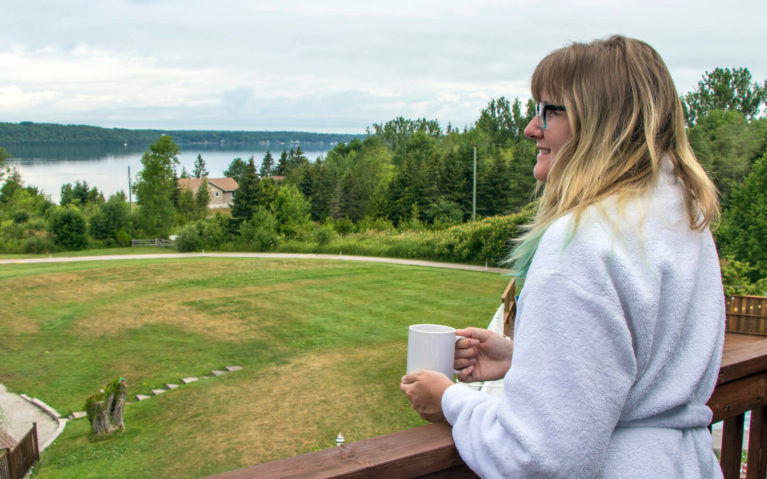 Lindsay Holding a Coffee Looking Over the Balcony at Georgian Bay at the Waterview Resort in Wiarton :: I've Been Bit! Travel Blog