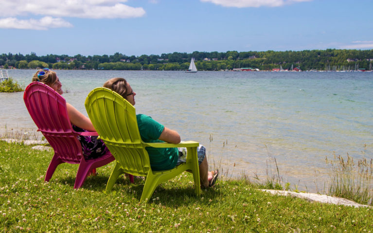 Lindsay and Robin Sitting in Muskoka Chairs on the Shores of Georgian Bay :: I've Been Bit! Travel Blog