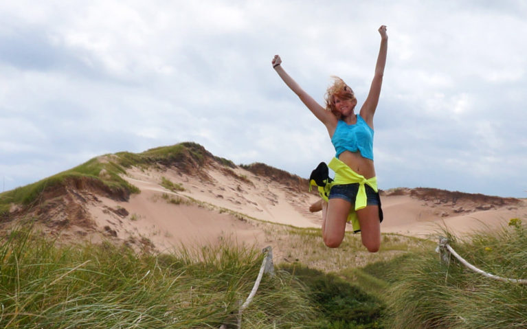 Lindsay Mid-Jump in Front of the Greenwich Sand Dunes in Prince Edward Island :: I've Been Bit! Travel Blog