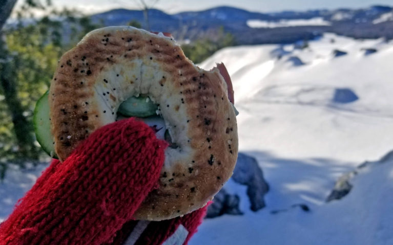 Mitten Holding Bagel Sandwich with Snowy Scene in the Distance :: I've Been Bit! Travel Blog