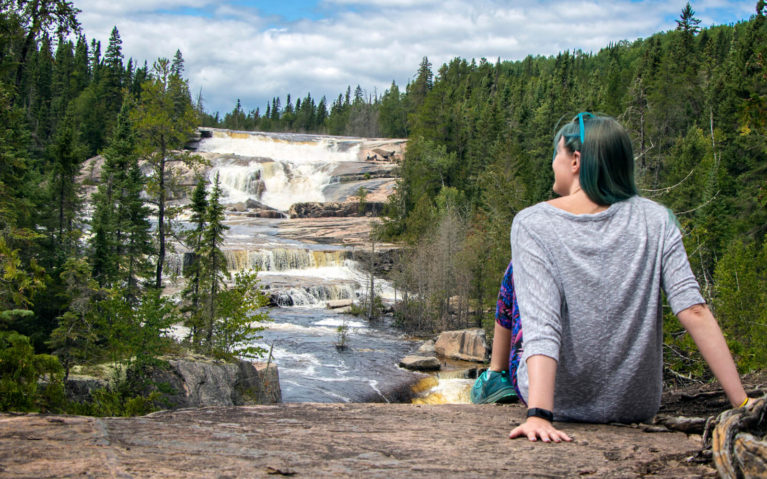 Lindsay Sitting on Ledge with Waterfall in the Distance :: I've Been Bit! Travel Blog