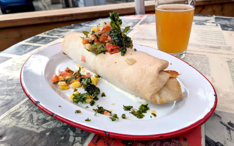 Burrito on a Plate with Garnish and a Beer in the Background :: I've Been Bit! Travel Blog