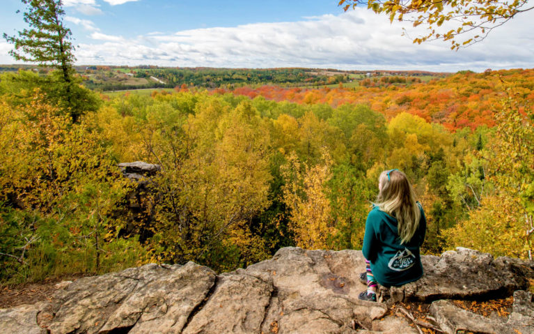 Lindsay Sitting On a Ledge at the Nottawasaga Bluffs Lookout :: I've Been Bit! Travel Blog