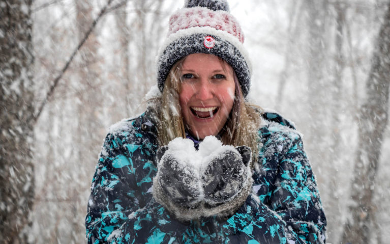 Lindsay Smiling in a Snowstorm While Holding Snow :: I've Been Bit! Travel Blog