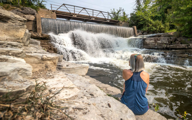 Lindsay Sitting In Front of Forest Mills Falls in Greater Napanee :: I've Been Bit! Travel Blog